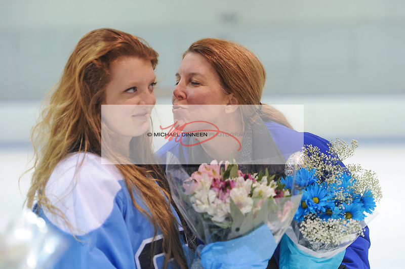 Despite the flowers, Chugiak Eagle River hockey mom Robin Bassett gets a less-than-welcome response to an on-ice kiss from daughter Savannah during the team's Senior Night ceremony at Ben Boeke Arena Monday, January 25th, 2016.  Photo for the Star by Michael Dinneen