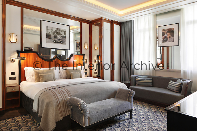 Hidden ceiling lights, wall lights and bedside lamps give this Claridges bedroom designed by Oliver Laws a warm glow