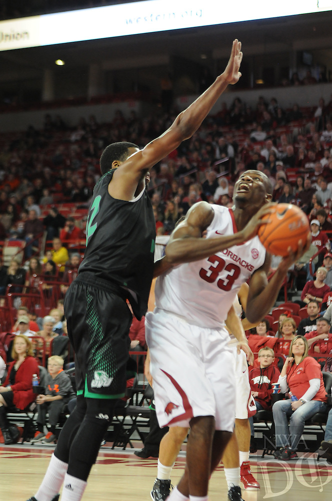 NWA Media/ J.T. Wampler -Arkansas' Moses Kingsley eyes the basket while Utah Valley's Chad Ross defends Saturday Jan. 3, 2015 at Bud Walton Arena in Fayetteville. The Hogs won 79-46.