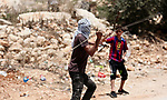 Palestinian protesters use a slingshot to hurl stones towards Israeli troops during clashes following a demonstration against the expropriation of Palestinian land by Israel in the village of Kfar Qaddum, near Nablus, in the occupied West Bank on June 22, 2018. Photo by Shadi Jarar'ah