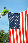 Fire fighter suspend an American Flag between two ladder trucks over the street for the 911 Memorial Ride in  Muncy,PA