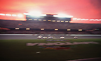 Cars race past the packed grandstands at sunset during the Pepsi 400 at Daytona International Speedway in July 2000. (Photo by Brian Cleary)