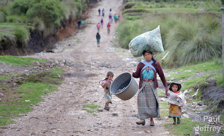 A woman walks along a road with her children in San Jose la Frontera, a small Mam-speaking Maya village in Comitancillo, Guatemala.