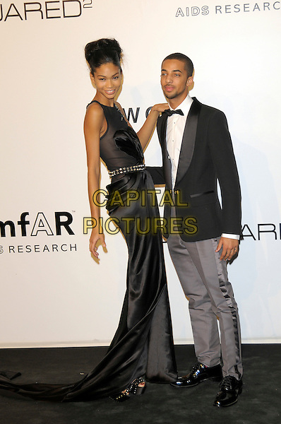 CHANEL IMAN & TYGA (Michael Stevenson).The amfAR Gala at La Permanente during the Mailand Fashion Week Spring/Summer 2010 - Milan, Italy. .September 28th, 2009.full length black dress grey gray trousers tuxedo jacket side hand on shoulder .CAP/RD.©Richard Dean/Capital Pictures.