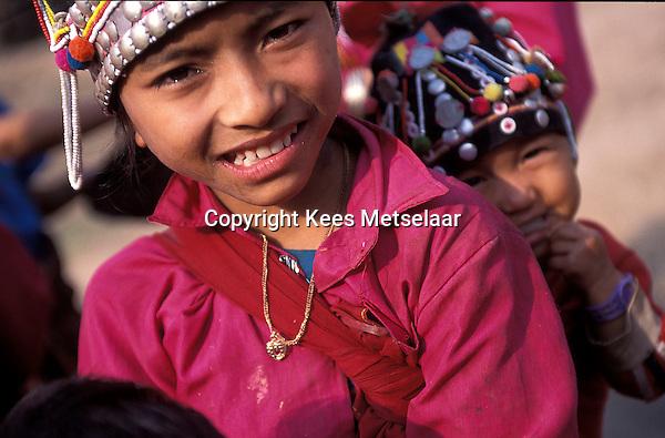 Laos, Luang Namtha Province, Ban Nammat Gao village..Young Akha girl, kid on back..Photo by Kees Metselaar, 2003