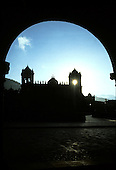 Cusco, Peru. Plaza de Armas through an arch with the sun behind the cathdral.