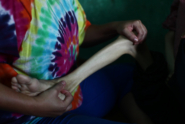 Kristen Vetter, a nurse and daughter of U.S. war veteran Larry Vetter, conducts physical therapy with La Thanh Toan, 21, at his home near Da Nang, Vietnam. Toan and his 18-year-old brother Nghia are third generation victims of dioxin exposure, the result of the U.S. military's use of Agent Orange and other herbicides during the Vietnam War more than 40 years ago. The brothers were born healthy but began to suffer from muscular dystrophy and other problems as they grew older. Now they are confined at home as their bodies and lives waste away. The Vietnam Red Cross estimates that 3 million Vietnamese suffer from illnesses related to dioxin exposure, including at least 150,000 people born with severe birth defects since the end of the war. The U.S. government is paying to clean up dioxin-contaminated soil at the Da Nang airport, which served as a major U.S. base during the conflict. But the U.S. government still denies that dioxin is to blame for widespread health problems in Vietnam and has never provided any money specifically to help the country's Agent Orange victims. Jan. 5, 2013.