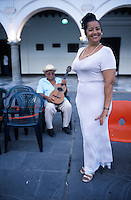 A Danzon dancer poses for a photograph in the central plaza of Veracruz where live bands play Danzon for the public to dance.  The couples who dance range in ages from children to the elderly.  A ¨jaranero¨musician rests in the background
