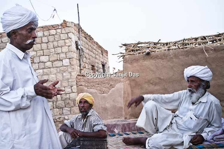 66-year-old Manganiyar artist, Lakha Khan speaks to his brothers outside their house in Raneri village of Jodhpur district in Rajasthan, India. Photo: Sanjit Das/Panos