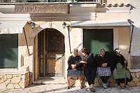 Elderly Corfiot women wearing traditional black clothes sitting relaxing in village square of Krini, Corfu, , Greece