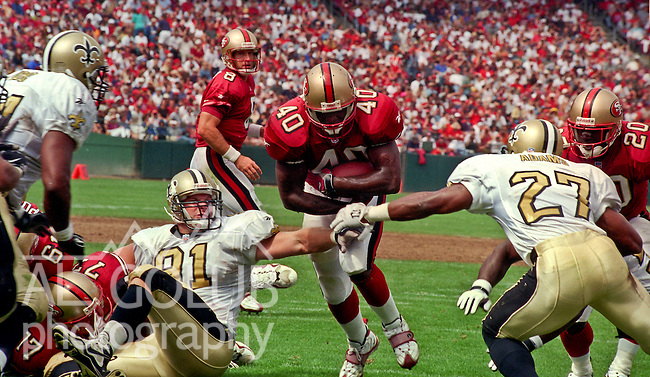 San Francisco 49ers vs. New Orleans Saints at Candlestick Park Sunday, September 14, 1997.  49ers beat Saints  33-7.  San Francisco 49ers full back William Floyd (40) runs through New Orleans Saints defensive end Brady Smith (91) and defensive back Vashone Adams (27).