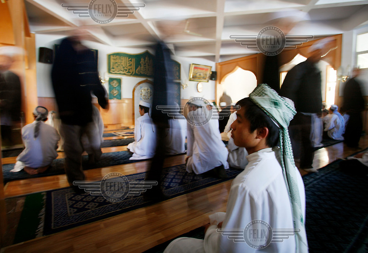Hui Muslim student waits while adults exit the prayer hall at the Xiguan Mosque.