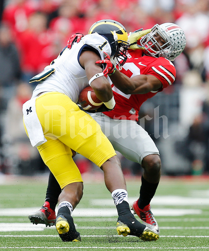Michigan Wolverines wide receiver Devin Funchess (1) tries to fight off Ohio State Buckeyes cornerback Doran Grant (12) in the second quarter the college football game between the Ohio State Buckeyes and the Michigan Wolverines at Ohio Stadium in Columbus, Saturday morning, November 29, 2014. As of half time the Ohio State Buckeyes and Michigan Wolverines were tied 14 - 14. (The Columbus Dispatch / Eamon Queeney)