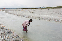 India – West Bengal: A former tea worker looking for pebbles and stones along the Diana riverbed at Red Bank Tea Estate, in the Dooars region. The garden, which houses 888 workers out of a population of 5,000 people, has been closed since 2013, forcing its workers to resort to stonecrushing along the riverbanks in order to survive. At the end of 2014, the tea estate was taken over by the government, in order to initiate emergency relief procedures for its population.