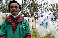 RUANDA, Kigali, plastic recycling bei Firma Ecoplastics, Plastikmuell, Trocknung von alten gereinigten Folien bevor sie zu Granulat recycelt werden, Arbeiter Jean De Dieu, 22 Jahre