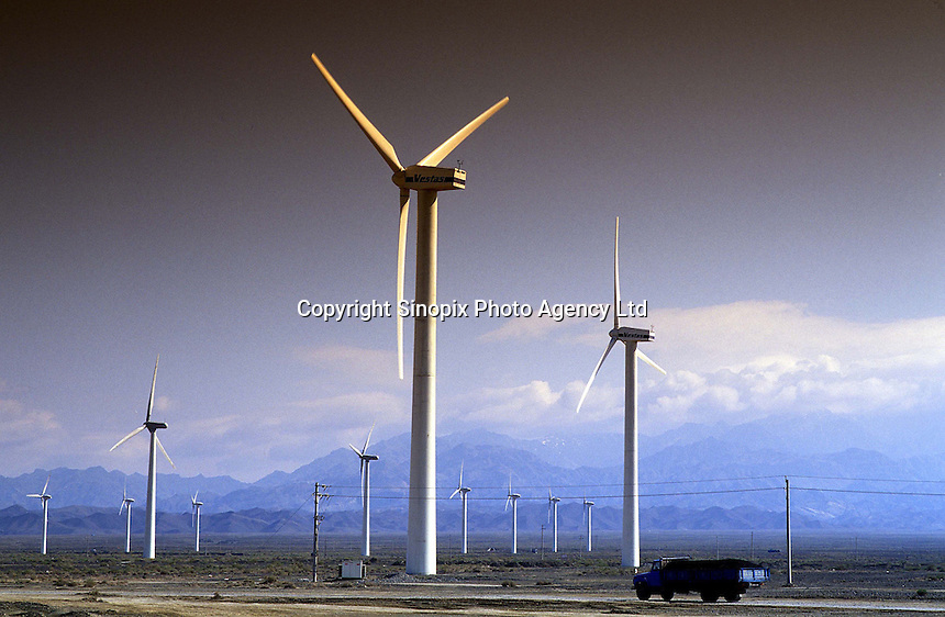A coal truck heading towards the Xinjiang capital Urumchi passes a farm of wind generators which offer an alternative source of energy to fossil fuels. The windmills are powered by strong winds coming off the Altai mountains in NW China..