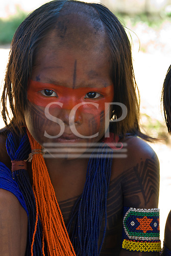 Pará State, Brazil. Aldeia Pukararankre (Kayapo). Girl with face and body paint and bead adornments.