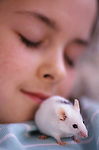 Young girl (9 years old) sleeping with pet mouse on her shoulder Marysville Washington State USA