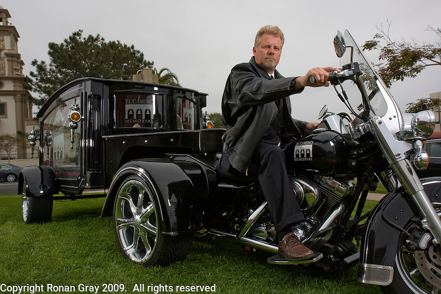 "May 29 2009, Pacific Beach, California, USA.  Douglas G. Trobaugh of Pacific Beach Chapel Funeral Home sits on his Harley Davidson Trike Hearse.  Nicknamed ""The Last Ride"", the hearse is becoming a popular choice for the funerals of local bike enthusiasts."