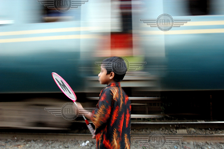 A child living in a Dhaka slum plays a game of badminton as a train rushes past. Many slums have grown up along railway tracks and accidents involving slum dwellers are common.