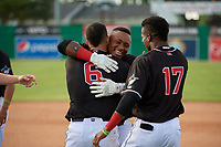 Batavia Muckdogs Albert Guaimaro (13) hugs Igor Baez (6) and Dalvy Rosario (17) after a walk off single during a NY-Penn League game against the Auburn Doubledays on June 19, 2019 at Dwyer Stadium in Batavia, New York.  Batavia defeated Auburn 5-4 in eleven innings in the completion of a game originally started on June 15th that was postponed due to inclement weather.  (Mike Janes/Four Seam Images)