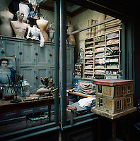 A view into a workshop, storage room with tailor's dummies, mannequins, neatly arranged bolts of folded fabric and a painted cupboard unit.