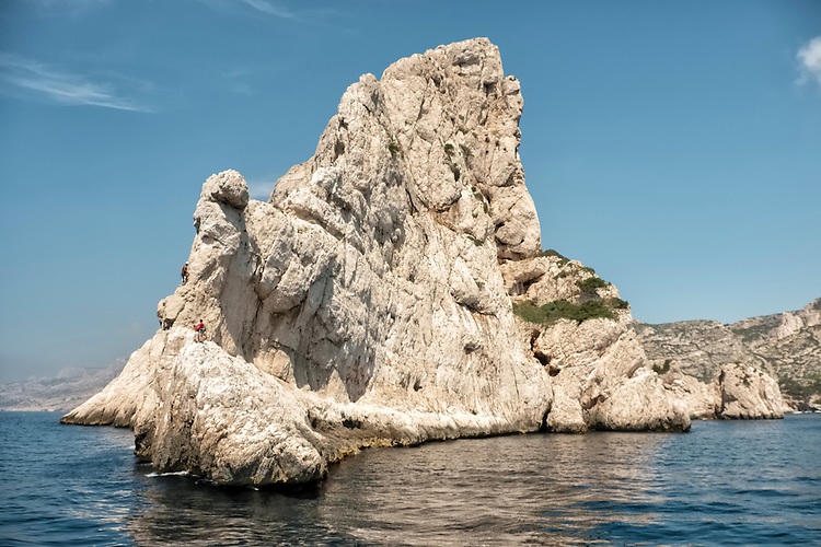 Intrepid climbers take on one of the limestone pinnacles along the French coastline known as Les Calanques.