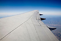 A close up of an airplane wing against blue sky.