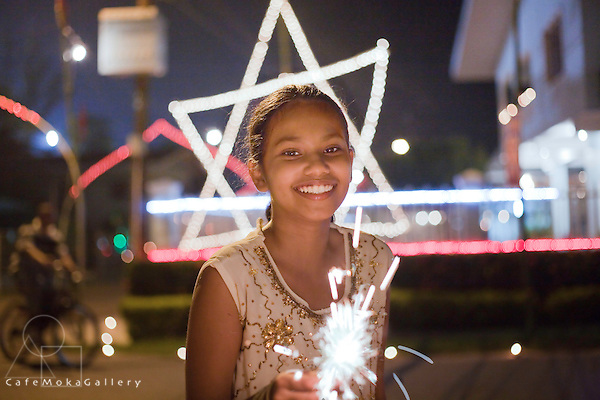 Divali,Hindu festival of light, beautiful young Trini-Indian girl with  a starburst from a deya