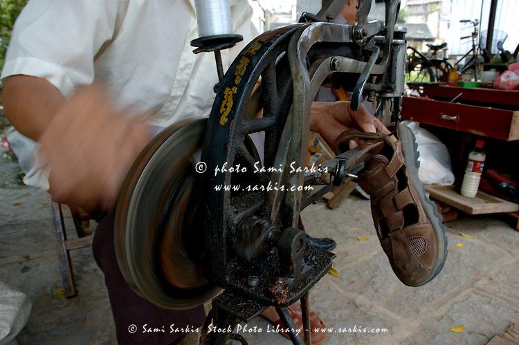 Shoemaker resoling a sandal, Yangshuo, Guangxi, China.