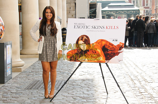 Lauren Goodger.PETA Sexy anti-exotic photocall, Covent Garden, London, England..April 3rd, 2012.full length white jacket blazer print dress beige lace shoes poster hand on hip.CAP/CJ.©Chris Joseph/Capital Pictures.