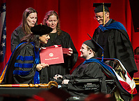 NWA Democrat-Gazette/BEN GOFF @NWABENGOFF<br /> Kim Needy, a University of Arkansas dean, presents a diploma to Raymond Walter, escorted by his doctoral adviser professor Laurent Bellaiche, Saturday, May 11, 2019, during the University of Arkansas all university commencement ceremony in Bud Walton Arena in Fayetteville. Walter received a Ph. D. in physics.