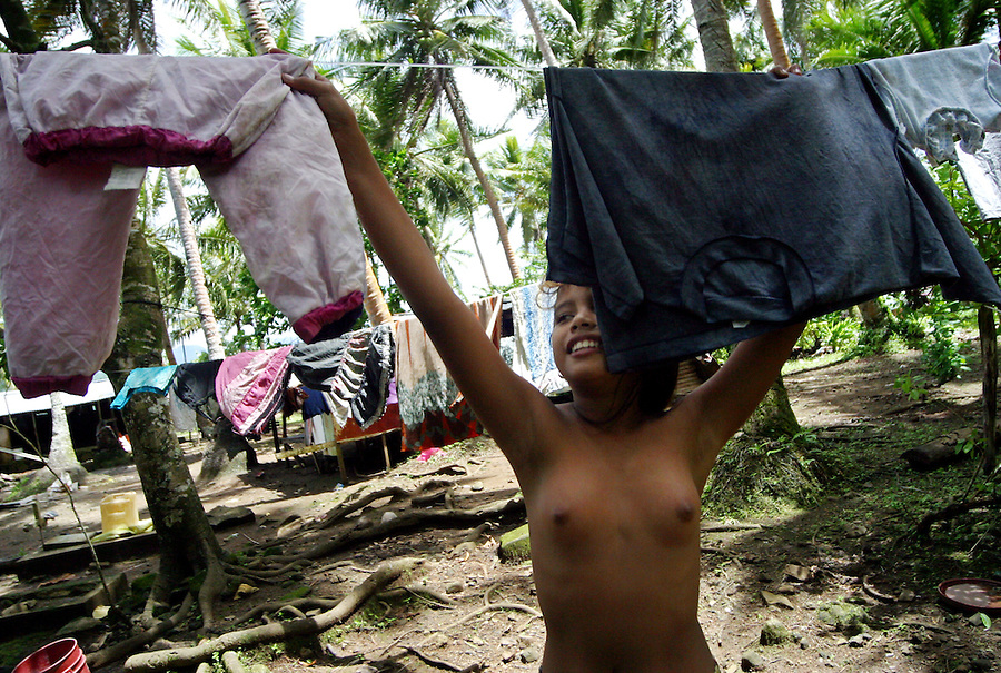 A young girl hangs up laundry on a clothes line in the Federated States of Micronesia.