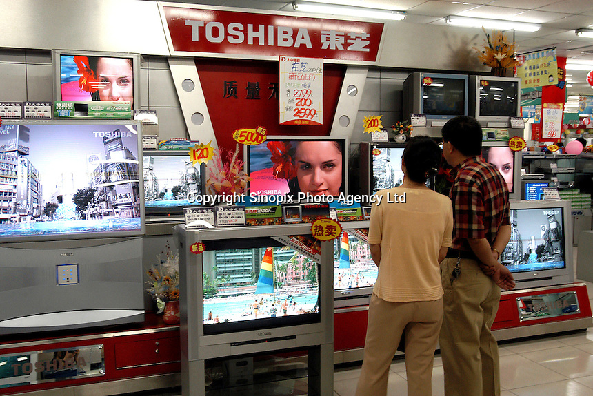 Shoppers look at Toshiba large-screen TV's that are on sale at a Beijing store. Toshiba Corp. and other foreign-brand TV sets that used to be priced beyond the means of most Chinese workers have dropped in price by as much as a third..07-JUL-03