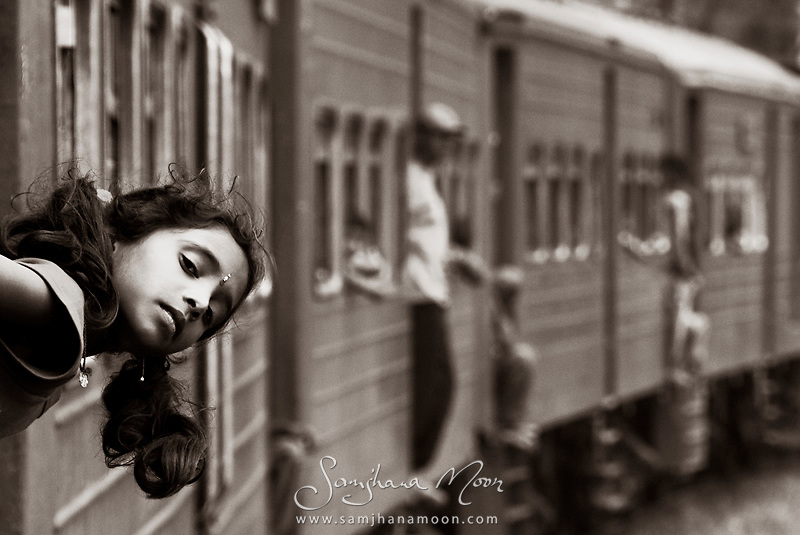 """""""A journey on the Sri Lankan Railway offers a whole new insight to the culture. Travelling at a maximum of 30 mph you can watch the world go by. The trains themselves are like giant toys with real people inside. As I was hanging out the window with my camera to my eye, this little girl appeared in my frame. Once she realised I was holding a camera, she retrieved her younger brother and moments later appeared smiling and waving from the carriage door."""""""