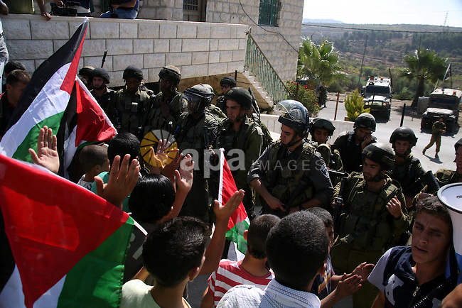 Israeli soldiers stand guard as Palestinian protestors demonstrate against the Israeli occupation in farm land close to the Palestinian village of Beit Omar near the Israeli settlement of Karmi Tsour, north the West Bank town of Hebron on September 30, 2011. Photo by Mamoun Wazwaz
