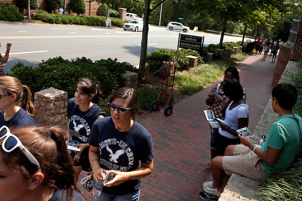 """August 20, 2011. Chapel Hill, NC.. American Eagle student """"brand ambassadors"""" and volunteers walk past the freshmen dorms as they spread awareness of the brand by helping incoming students move in and give away coupons.. Many companies have increased their efforts to reach the youth market by employing popular college students to raise the awareness of the brand by peer to peer marketing on campus' around the country."""