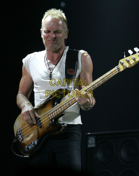 STING - THE POLICE.Live during their 2007 Tour in Anaheim, California, USA.. June 21st, 2007                                                                    .**Editorial Use Only**.half length stage concert gig performance music gordon sumner bass white sleeveless top funny face .CAP/EST.©Eastman/Capital Pictures