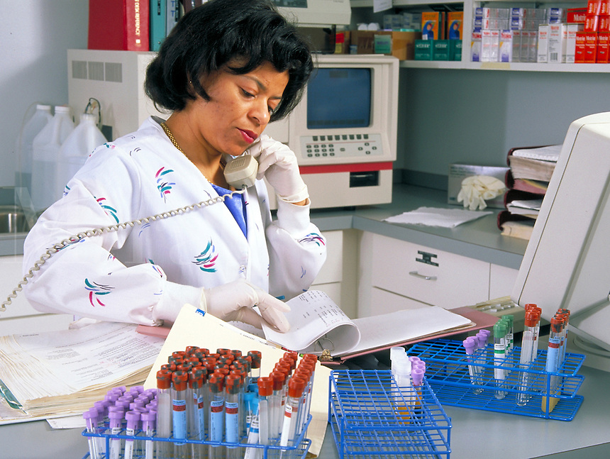 African-American female nurse talks on phone and reviews medical records in lab area with computer and test tubes visable. nurse.