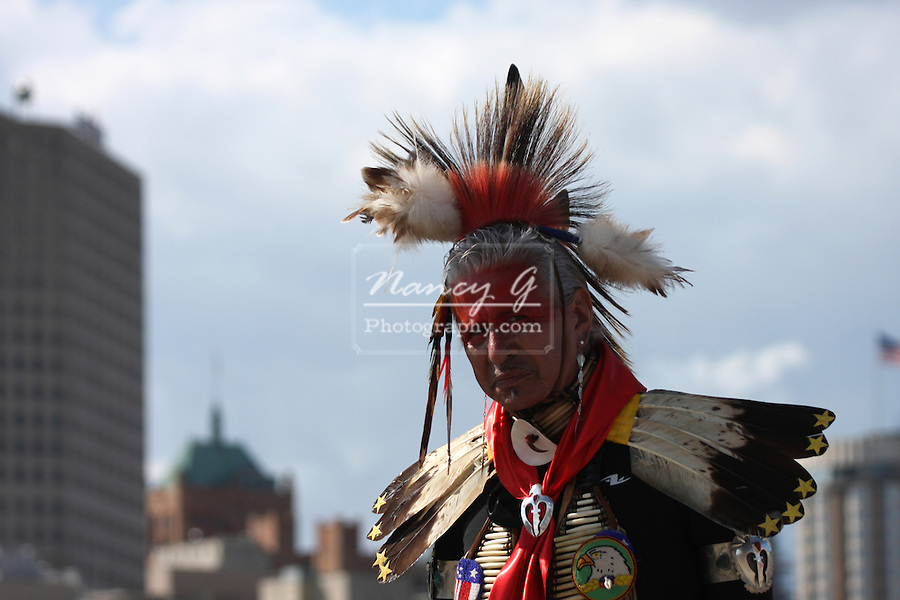 A Native American Indian man standing in front of the buildings at the lake front of Lake Michigan, Milwaukee Wisconsin