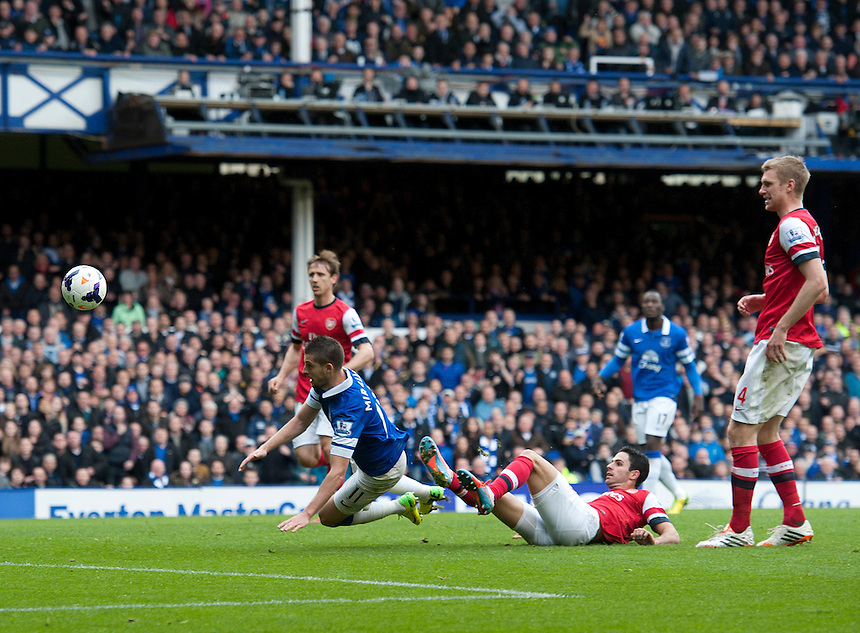 Arsenal's Mikel Arteta (grounded) is credited with an own goal, Everton's third as he put under pressure by Everton's Kevin Mirallas<br /> <br /> Photo by Stephen White/CameraSport<br /> <br /> Football - Barclays Premiership - Everton v Arsenal - Sunday 6th April 2014 - Goodison Park - Liverpool<br /> <br /> &copy; CameraSport - 43 Linden Ave. Countesthorpe. Leicester. England. LE8 5PG - Tel: +44 (0) 116 277 4147 - admin@camerasport.com - www.camerasport.com