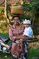 Bali, Indonesia.  Balinese Hindu Mother and Son on their Way to the Temple.  Pura Dalem Temple, Dlod Blungbang Village.