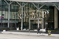 Woman walking past the  entrance to Trump International Hotel and Tower on Georgia Street in downtown Vancouver, British Columbia, Canada
