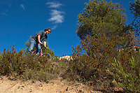 Man riding his mountain bike on a dirt path through bushes, Vitrolles, Provence, France.