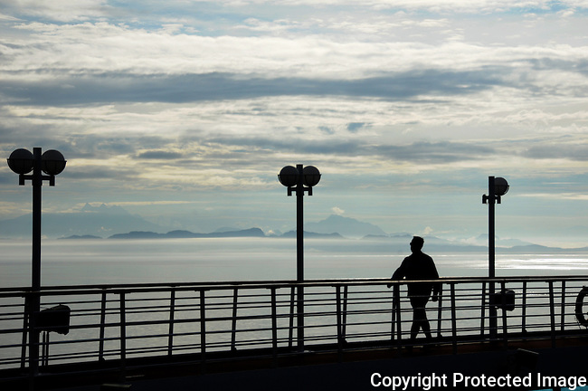 silhouetted man walks along top deck of cruise ship on a cloudy early morning off s Alaska coast