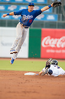 Tulsa Drillers infielder leaps in attempt to make a catch on a throw as Northwest Arkansas Naturals infielder Travis Jones (27) safely slides into second on May 13, 2019, at Arvest Ballpark in Springdale, Arkansas. (Jason Ivester/Four Seam Images)