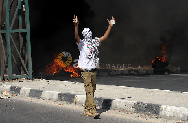 A Palestinian protester reacts during clashes with Israeli troops following a protest in solidarity with Palestinian prisoners held in Israeli jails, at the Hawara checkpoint near the West Bank city of Nablus on Aug. 18, 2016. Photo by Nedal Eshtayah