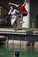 Moscow, Russia, 25/06/2010..Teenagers dive into fountains next to the Kremlin and Red Square during a heatwave that has seen temperatures of up to 37C, a record for the month of June.