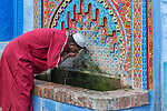 A traditional dressed Moroccan man drinks water from a fountain in the old town (medina) of Chefchaouen in Morocco.