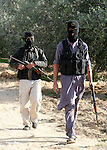 """Palestinian militants walks  following an exchange of fire with Israeli troops in Khan Younis, southern Gaza Strip. Palestinian gunmen clashed with Israeli troops on Friday along the Gaza-Israel border, as persistent violence chipped away at a soon-to-expire truce. The Israeli military said troops identified a group of gunmen in southern Gaza trying to place an explosive device along the security fence that separates the coastal strip from Israel. the arabic on wall reads """"resistance."""""""